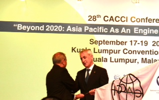 Asian-Pacific business leaders shake hands at the 28th CACCI Conference in Kuala Lumpur.