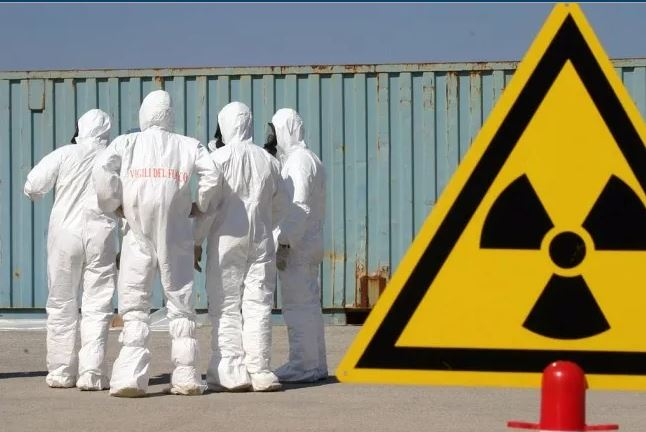 Italian firefighters dressed in CBRN suits set up a perimeter of warning signs.