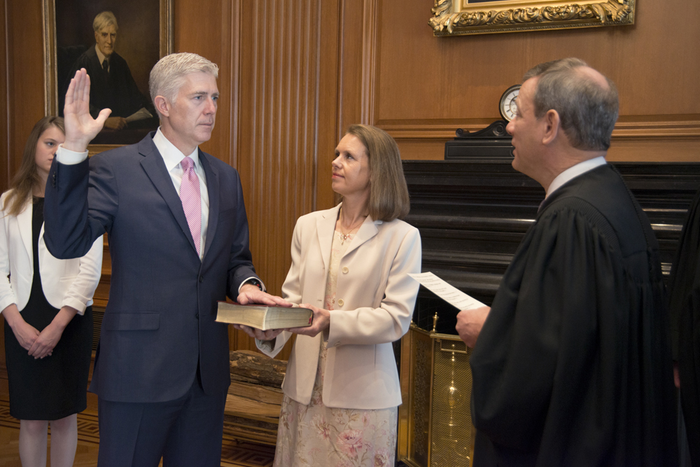 Neil Gorsuch (left) is administered the oath of office by Chief Justice John Roberts (right).