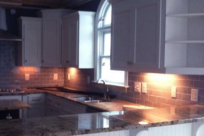 Under-cabinet lighting illuminates workspaces in the kitchen.