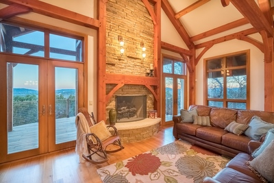 The home includes a spacious living room with rustic Douglass Fir wood beamed ceiling and a striking floor-to-ceiling stone fireplace.
