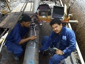 Technicians inspect a PETRONAS pipe using NDT methods in order to test the quality of the pipeline.