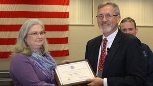 Babbette Harman is presented a Secretary of Homeland Security Award for Unity of Effort for her service in the Ebola Worldwide Response effort from CDP Superintendent Mike King.