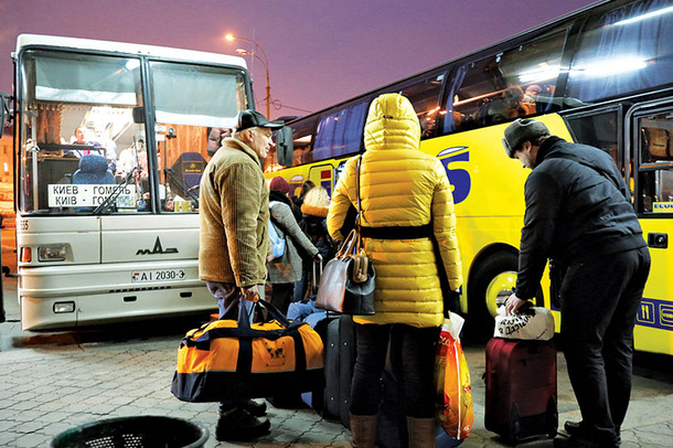 People at the Kyiv central bus station prepare to board a bus Wednesday. More people are using carpooling services to link up with other drivers to save money.
