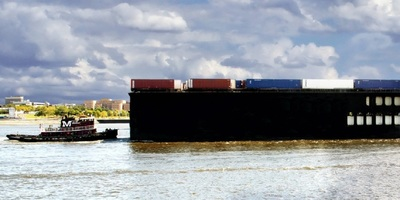 A tugboat guides a container barge on the Delaware River at the Port of Philadelphia
