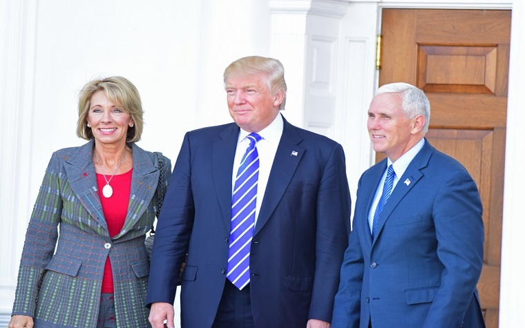 Betsty DeVos with Donald Trump and Mike Pence