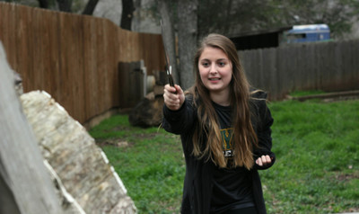 Ready, aim, throw: Brooke Landry works on her technique as she throws a knife at the target during her practice time. Landry has her own section of her backyard with targets to practice her knife throwing.