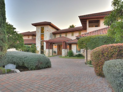 The landscaping ensures privacy while adding a lush backdrop to the stone and stucco structure.