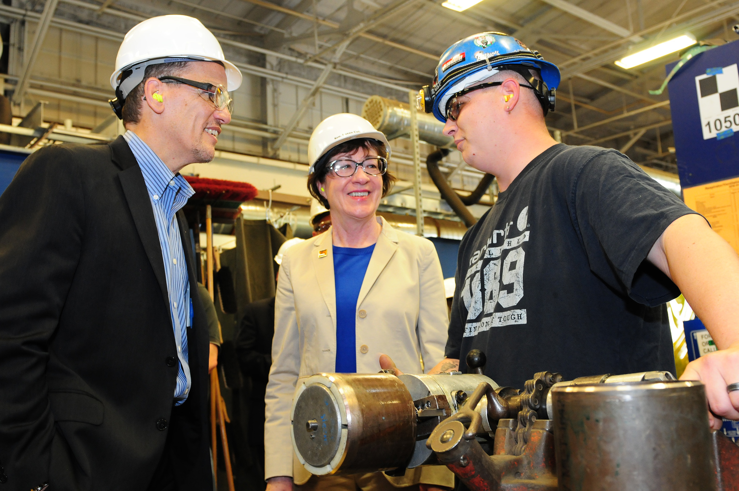 The U.S. Secretary of Labor, Thomas Perez and U.S. Senator Susan Collins (R-Maine) talk with Derek Farrington of Brunswick, Maine, an apprentice at the Trades Learning Center at Bath Iron Works.