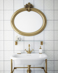 An antique mirror and brass fixtures give this bathroom a vintage feel.