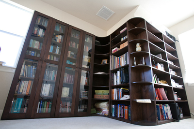 This custom shelving unit features a glassed-in case and curved shelving around a corner wall.