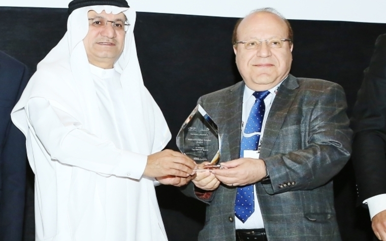 Humaid Al Qatami, director-general of DHA, hands over the award to Hussein Anani, COO of Canadian Specialist Hospital.